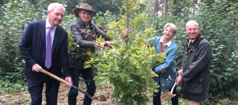 Tim Oliver (left) plants one of Surrey's 1.2 million new trees